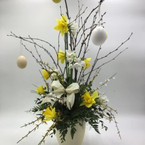 a ceramic Egg filled with seasonal spring blooms; branches in bud and hanging Easter eggs